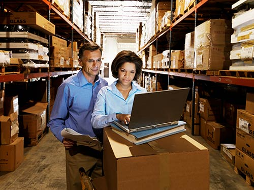 Woman in a warehouse looking up inventory on laptop